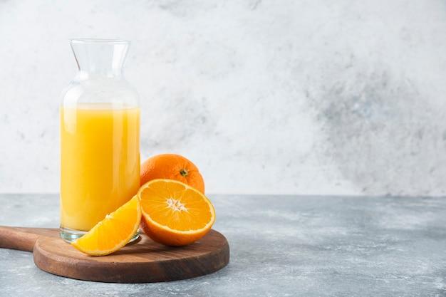 Glazen kruik sap met schijfje oranje fruit.