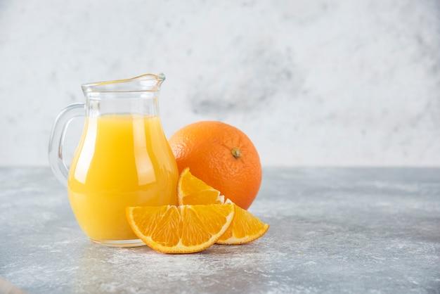 Glazen kruik sinaasappelsap met plakjes fruit.