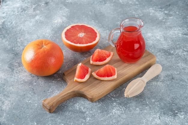 Glazen kruik vers grapefruitsap met plakjes fruit.