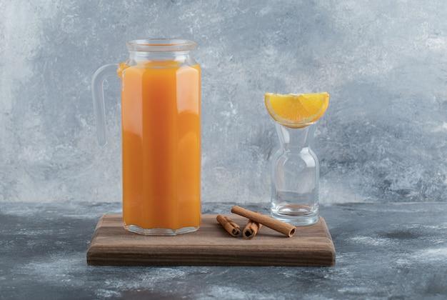 Glazen kruik vers sap en kaneelstokjes op een houten bord.