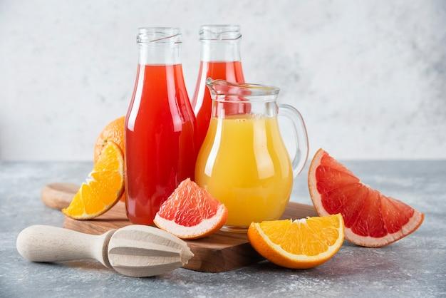 Glazen kruiken grapefruitsap met plakjes sinaasappelfruit.