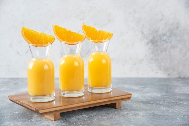 Glazen kruiken sap met plakjes oranje fruit op een houten snijplank.