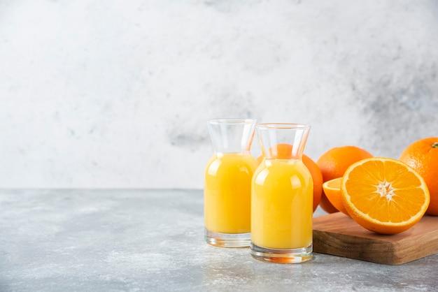 Glazen kruiken sap met schijfje sinaasappelfruit.