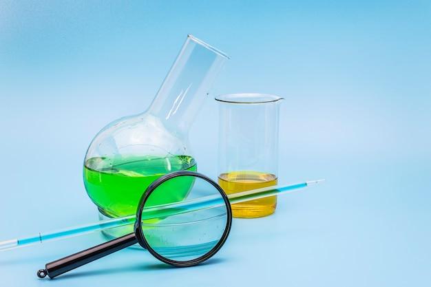 Glazen laboratoriumkolf en beker in een kopje met een groene en gele oplossing met een vergrootglas op een zachte blauwe medische achtergrond. het concept van medische en chemische analyses. ruimte kopiëren.