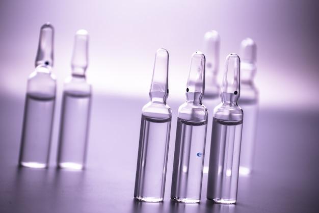 Glazen medicijn ampullen op een paarse muur close-up