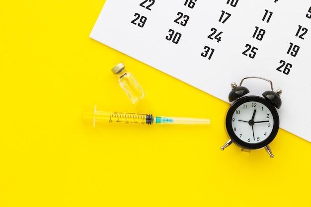 Glazen medicijnflesje met vloeistof en spuit, kalender en wekker op gele achtergrond. schema voor medische bloedingen. gezondheid concept. plat lag, bovenaanzicht met kopie ruimte.