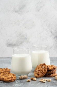 Glazen melk en zelfgemaakte koekjes met biologische pinda's op marmeren tafel.