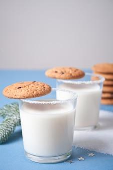 Glazen melk, koekjes, kerstboomtak op blauw