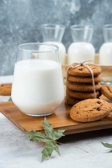 Glazen melk met chocoladekoekjes en bladeren.