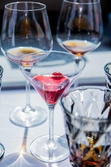 Glazen met alcohol en kers op witte talbe in restaurant.