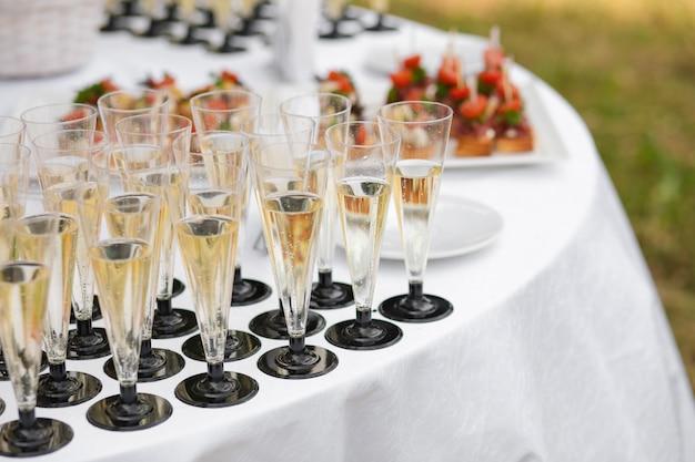 Glazen met champagne geserveerd op tafel in de buurt van voorgerechten