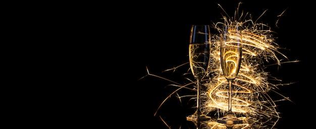 Glazen met champagne in het gouden licht van bengalen lichten