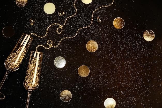 Glazen met champagne met gouden decor op een zwarte achtergrond plat lag vieringsconcept