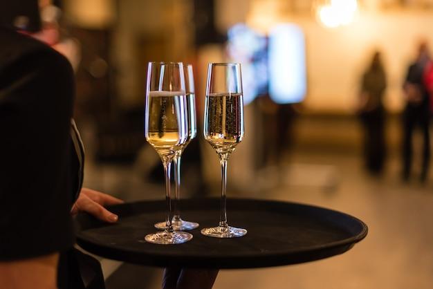 Glazen met champagne op een dienblad bij de ober