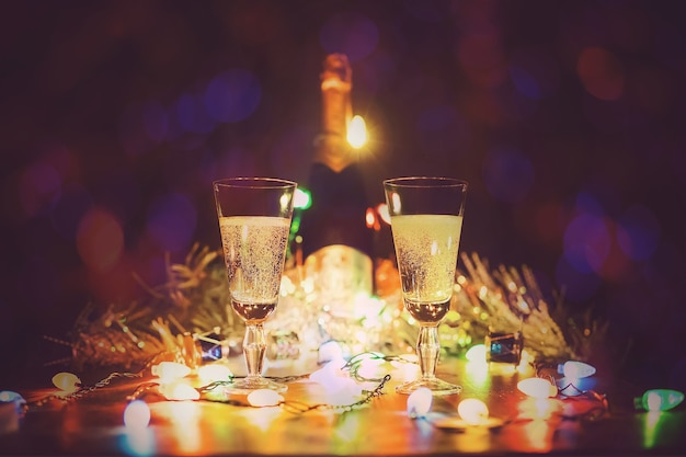 Glazen met champagne staan op een houten tafel tegen de achtergrond van lichten van een slinger. twee glazen champagne roosteren tegen bokeh lichten achtergrond