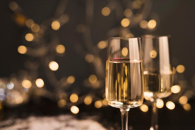 Glazen met drankje in de buurt van kerstverlichting