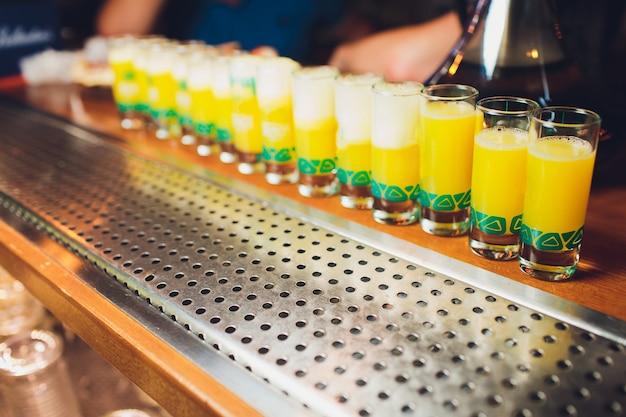 Glazen met een alcoholische drank op een vochtige glazen tafel.