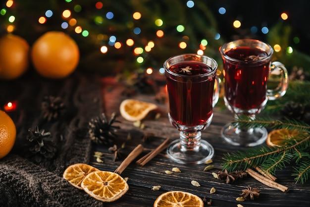Glazen met glühwein op een houten tafel versierd met een kerstboom