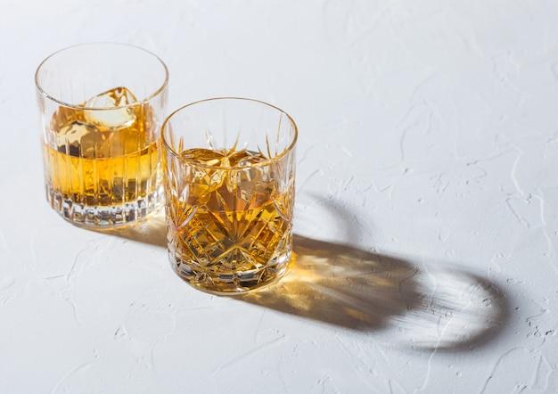 Glazen met ijsblokjes van single malt whisky op witte achtergrond met diepe schaduw.