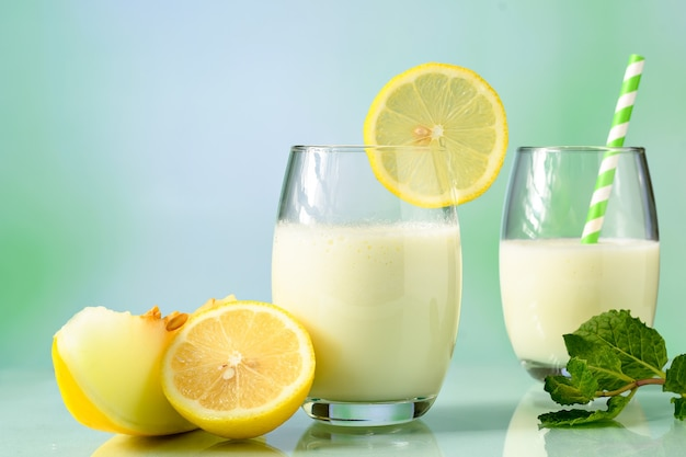 Glazen met meloensap met melk en siciliaanse citroen op reflecterend oppervlak