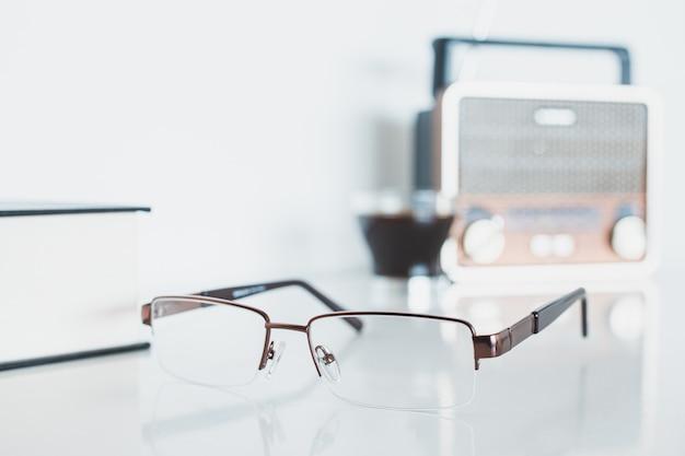 Glazen met radio, boek en koffie