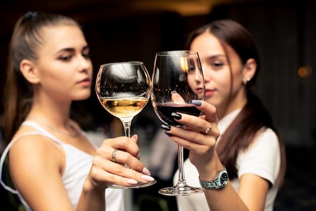 Glazen met rode en witte schuldig in de handen van mooie meisjes gekleed in witte blouses