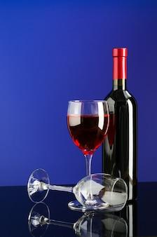 Glazen met rode wijn en fles wijn op heldere blauwe achtergrond met kopie ruimte voor uw tekst.