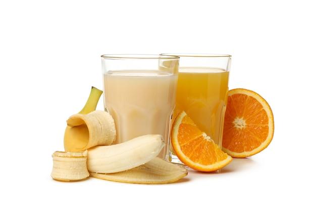 Glazen met sinaasappel- en bananensappen op wit wordt geïsoleerd