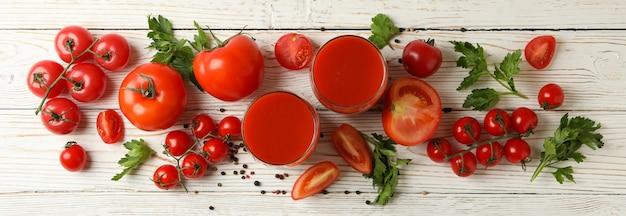 Glazen met tomatensap, tomaten en kruiden op een houten bord