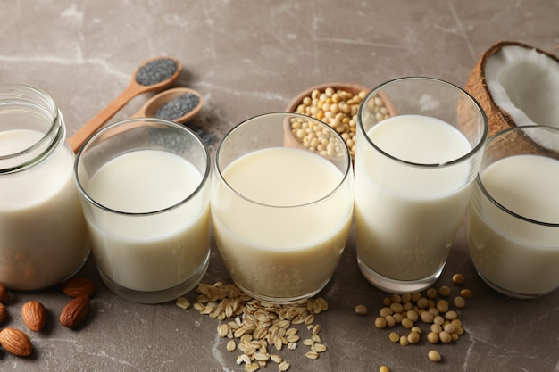 Glazen met verschillende soorten melk op bruin