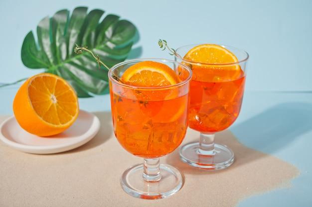 Glazen met verse zelfgemaakte sinaasappel zoete ijsthee of cocktail, limonade met tijm. verfrissend koud drankje. zomerfeest.