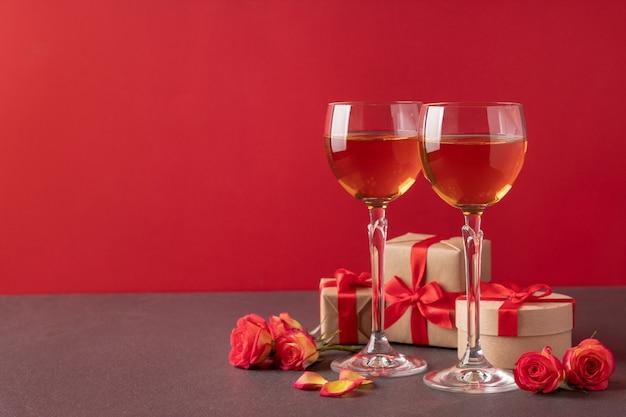 Glazen met wijn, geschenkdozen en rozen op tafel tegen rode achtergrond, kopieer ruimte. valentijnsdag