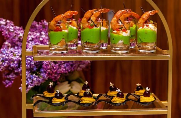Glazen met zeevruchten en groene pasta hapjes banket schotel voor evenementen en buffet