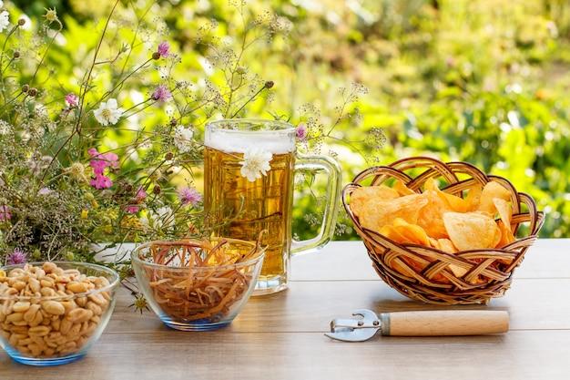 Glazen mok bier op houten tafel met chips in rieten mand, pinda's en gedroogde inktvis in kommen op natuurlijke groene onscherpe achtergrond