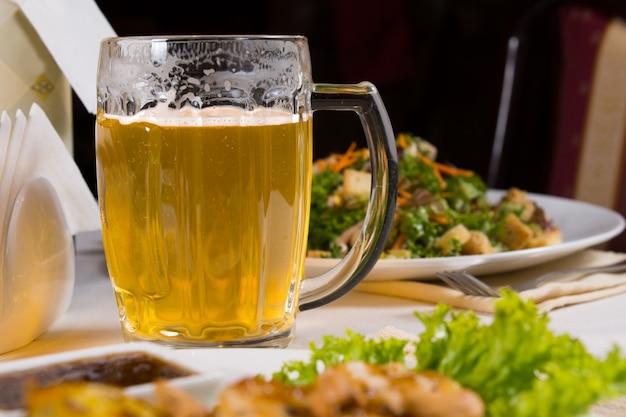 Glazen mok bier op tafel tussen borden met eten op tafel in restaurant