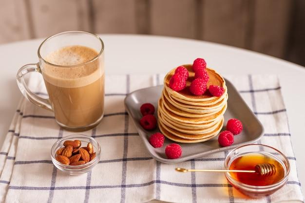Glazen mok met aromatische cappuccino, kommen met amandelnoten en honing, bord met stapel zelfgemaakte pannenkoeken met verse frambozen