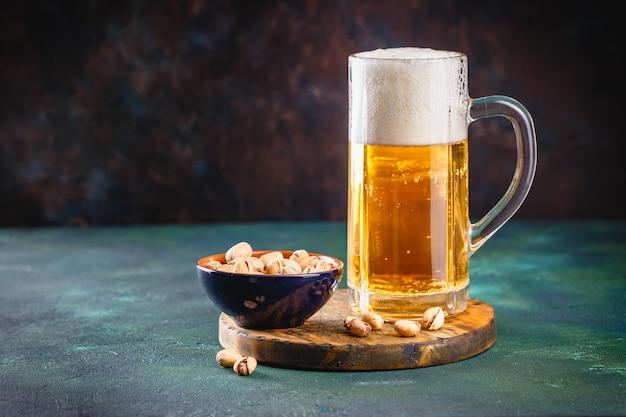 Glazen mok met bier met schuim en waterdruppels op donkergroen