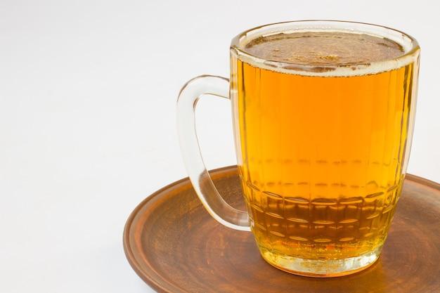 Glazen mok met bier op een keramische plaat.
