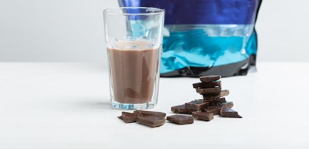 Glazen mok met een eiwitchocoladeshake staat tegen de achtergrond van een pakje eiwit op een witte tafel. sportvoeding concept.