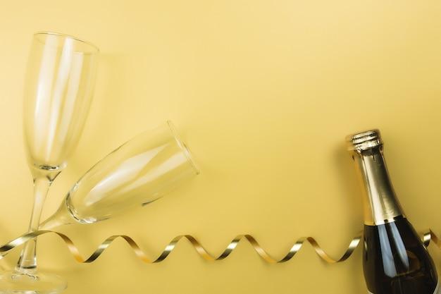 Glazen, mousserende wijnfles en gouden lint