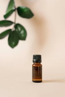 Glazen oliefles op een beige oppervlak, en een blad van tropische planten met defocus. biologische natuurlijke cosmetica