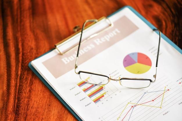 Glazen op diagramgrafieken bedrijfsgrafiekdocument document dat in het bureau werkt. bedrijfsrapport plan concept