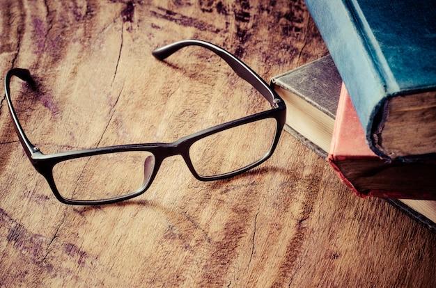 Glazen op een houten tafel met boeken geplaatst.