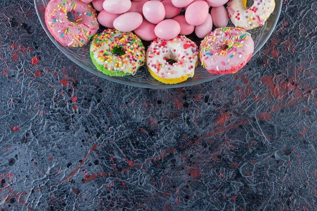 Glazen plaat van kleurrijke heerlijke donuts en roze snoepjes op donkere ondergrond.