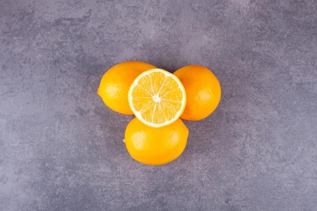Glazen plaat vol verse citroenen met bladeren op marmeren oppervlak.