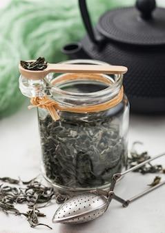Glazen pot biologische losse groene thee met vintage metalen zeef-infuser op lichte achtergrond met japanse ijzeren theepot en groene doek.