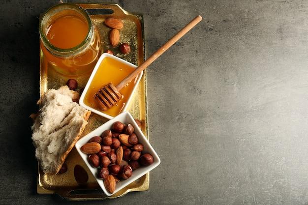 Glazen pot en kom met honing en noten op grijze tafel