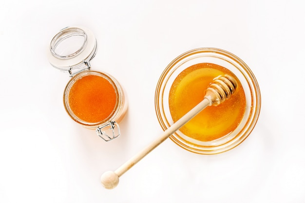 Glazen pot en schotel met honing en een lepel voor honing