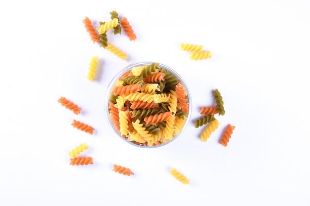 Glazen pot gevuld met droge rotini gele pasta over geïsoleerde wit