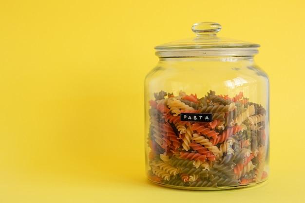 Glazen pot gevuld met kleurrijke spiraal pasta geïsoleerd op gele achtergrond